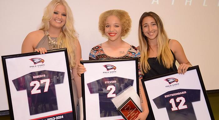 Maggie Roberts, Rose Stevens, and Stephanie Koutsoumbaris display replicas of their jerseys. Their numbers will be retired at the end of this season. (Photo by Tom Hagerty, Polk State.)