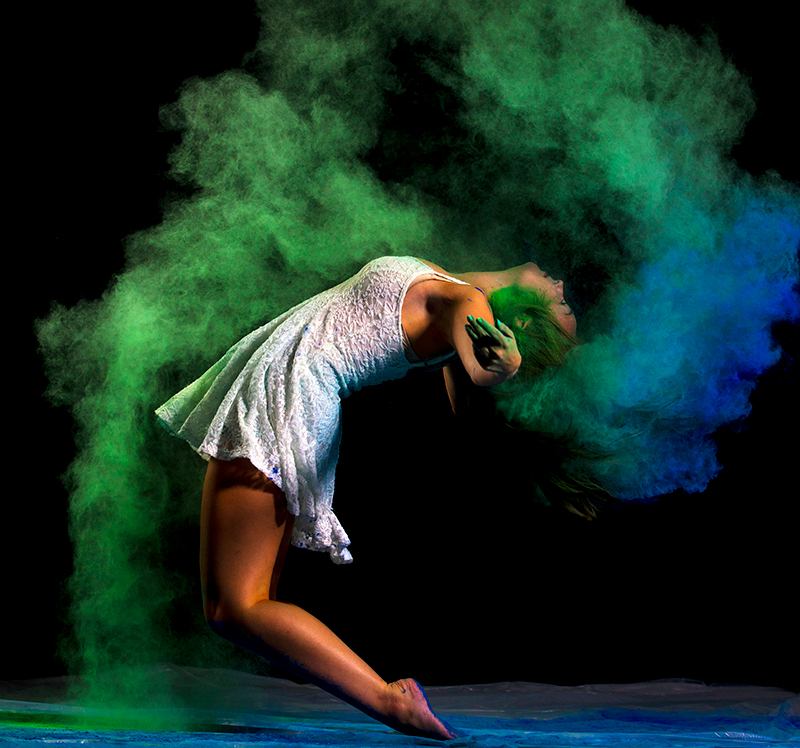 A dancer throws chalk in the air with her hair.