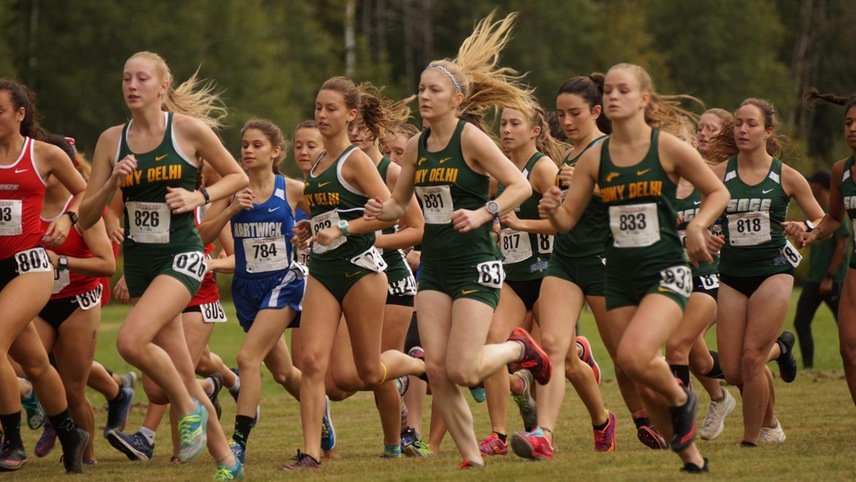 The women's cross country team runs out of the starting line.