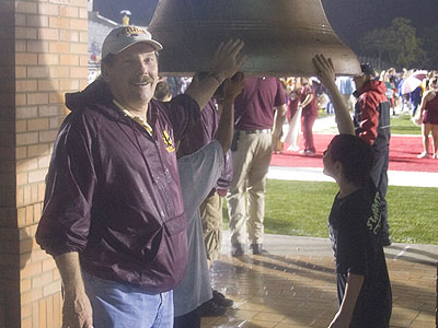 "Bulldog Alum Larry Marfechuk is shown near the new ""Victory Bell"" he helped restore last fall"