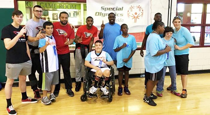 Eagles basketball players and coaches pose for a photo with Special Olympics athletes at a recent clinic.