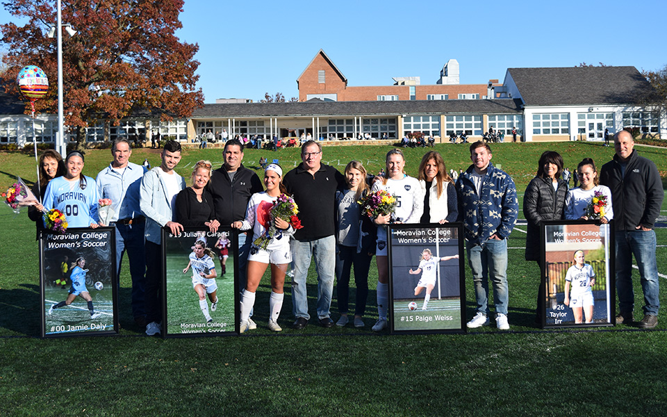 Seniors Julina Caranci, Jamie Daly, Taylor Irr and Paige Weiss with their families on Senior Day prior to playing Goucher College on John Makuvek Field.