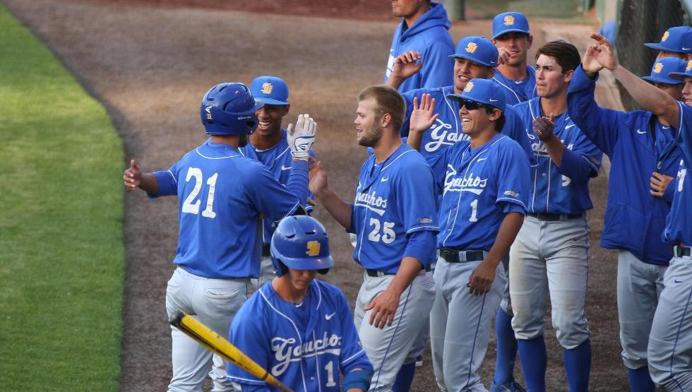 Andrew Calica, below, is greeted by teammates after clubbing a solo home run in the third inning (photo by Gerry Fall)