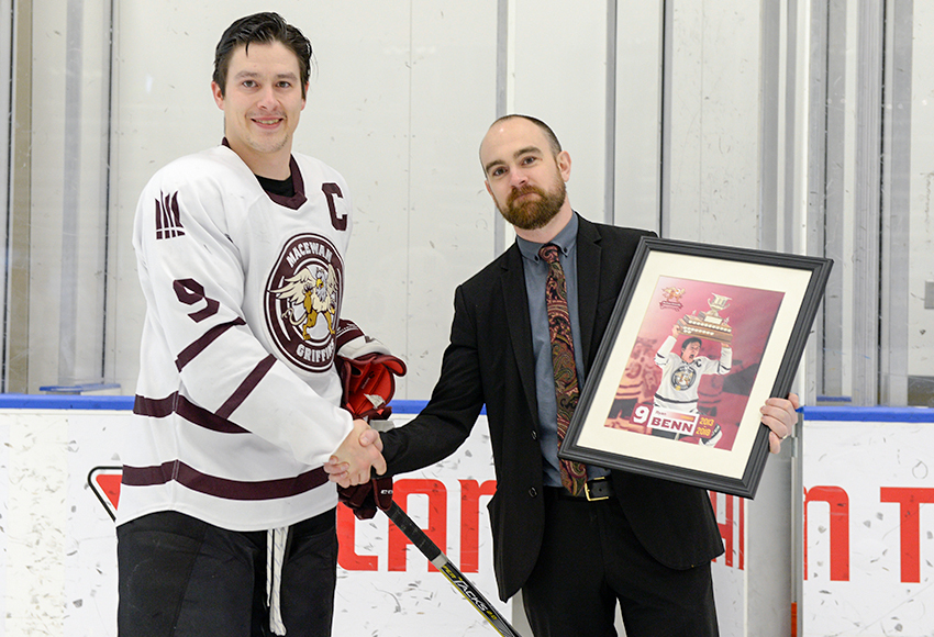 Ryan Benn receives a framed print from Griffins head coach Michael Ringrose prior to the final regular season game of his career in February.