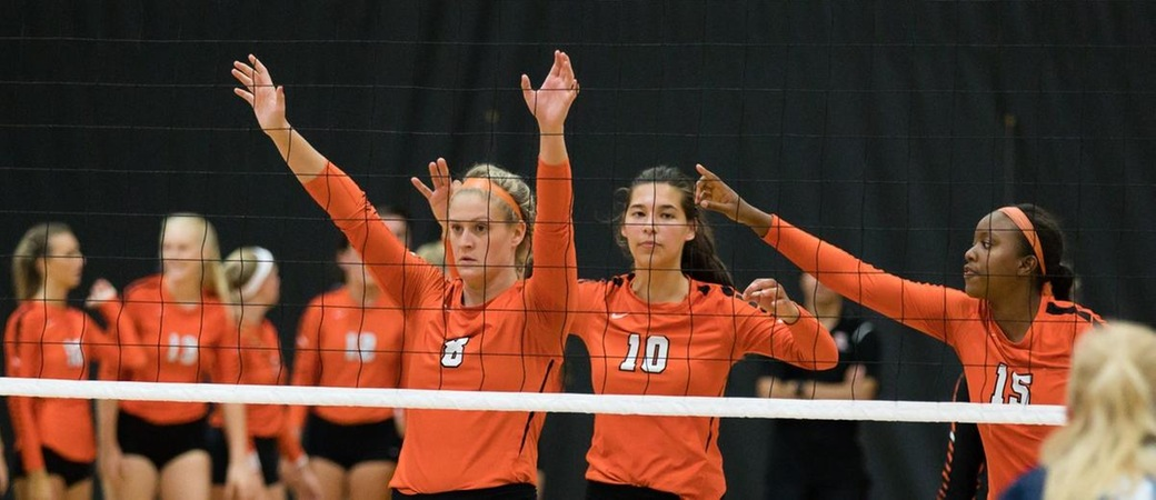 Kalamazoo College volleyball players at the net.