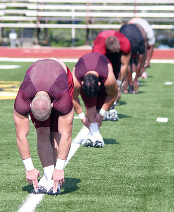 Bulldog players stretch at practice