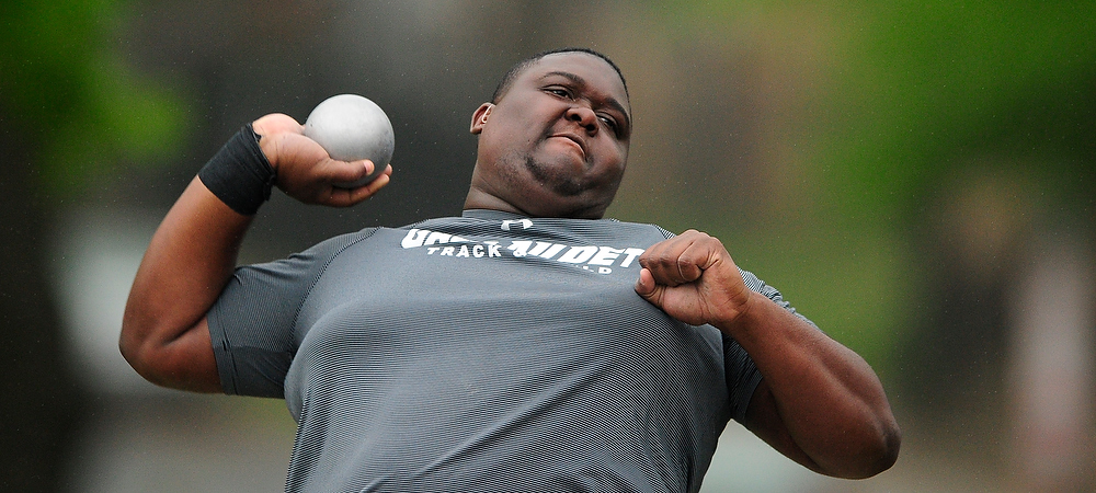 Gallaudet's Jaquan Thomas performs the shot put. He is wearing a gray colored t-shirt. the shot put is in the palm of his right hand. He is about to throw the shot with all his might.