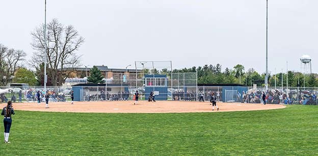 View of the softball field from the outfield looking in toward home plate. Several players are visible, and there are many people in the bleachers on both sides.