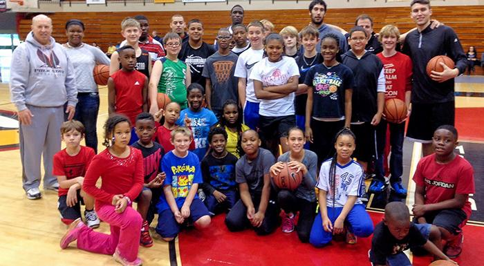 Eagles coaches and players pose with kids at clinic and free-throw contest.