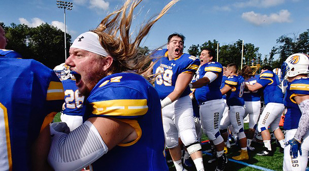 Misericordia players go crazy on the sidelines celebrating the win vs. Widener. (Misericordia athletics photo by Sean McKeag)