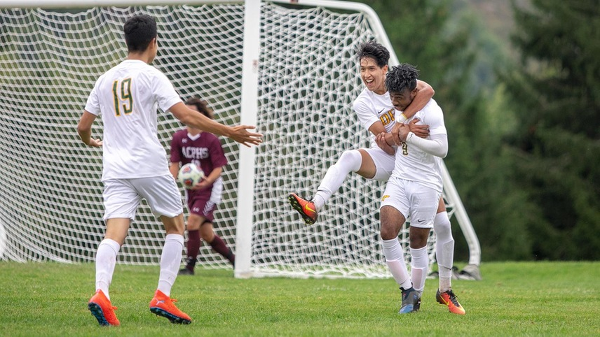Juan Velez with his arms around Denzel Monexant, celebrating after a goal.