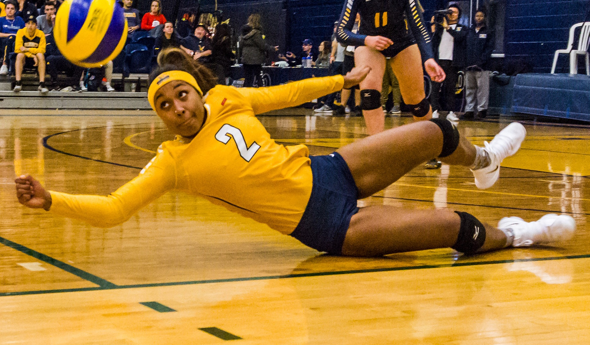 Humber women's volleyball player dives for the ball.