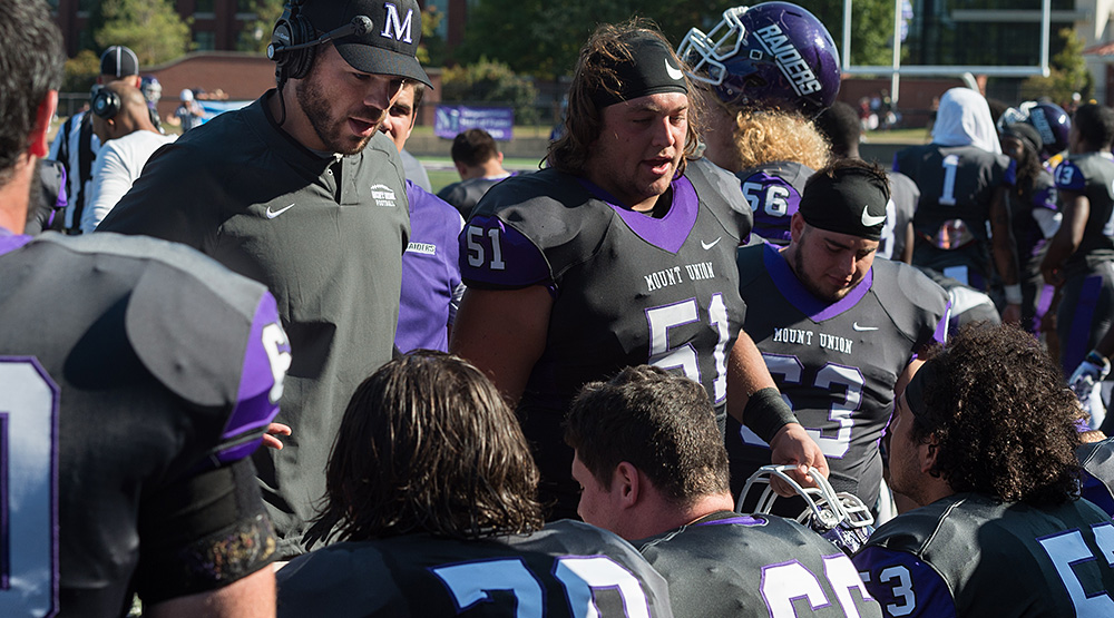 Cole Parrish talks to his fellow offensive linemen on the sideline.