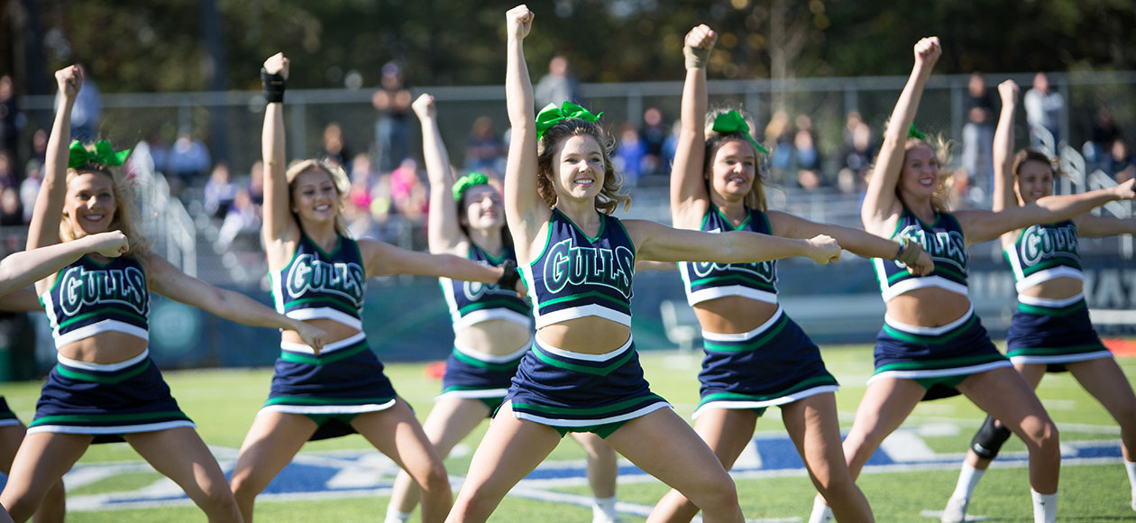 The cheer team cheers at halftime of a game.