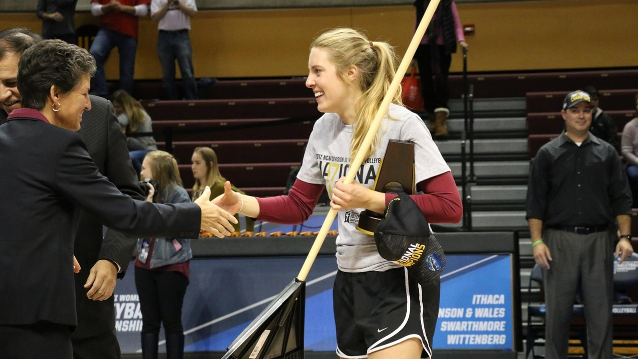 Jenny Smith receives her NCAA Championship medal, while holding the rake that became a symbolic part of the team's success
