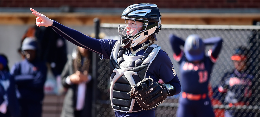 Gallaudet's Jenny Mendis communicates to her team while wearing her catcher's gear and her mask.