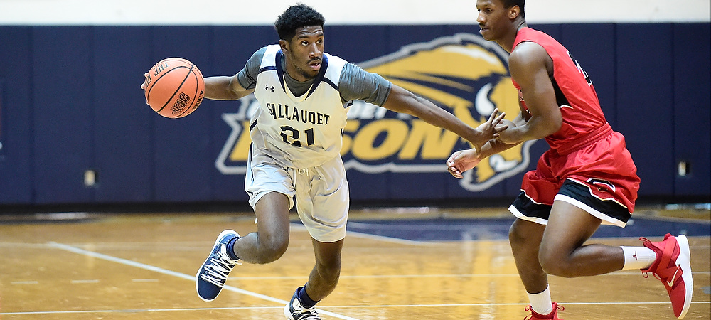 Gallaudet men's basketball guard Corey Smith dribbles with his right hand around a defender.