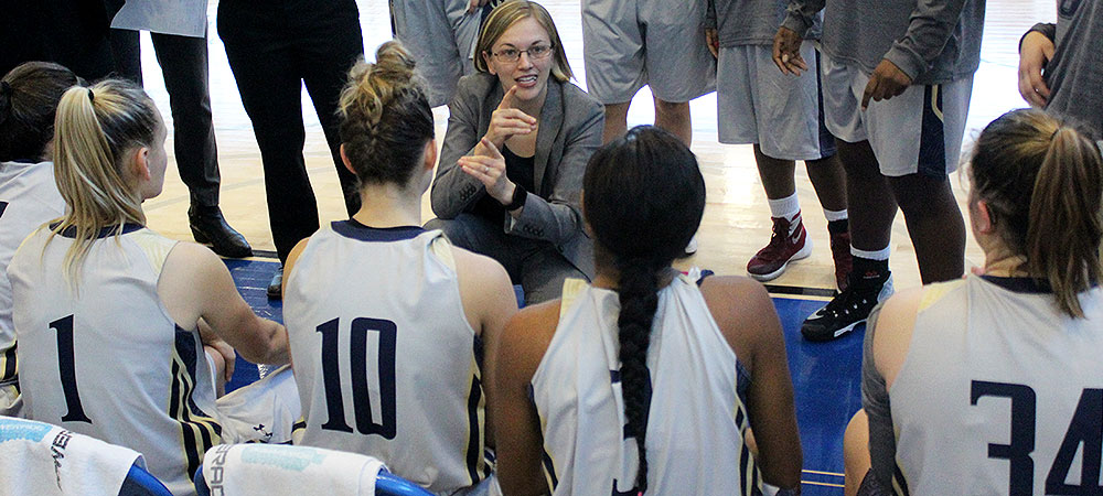 Gallaudet women's basketball coach Stephanie Stevens (center) is signing to her players during a timeout in a game. She is signing the word defense with her hands. She is looking at her five players that are sitting in folding chairs. The players' backs are to you. They are wearing gray colored jerseys.