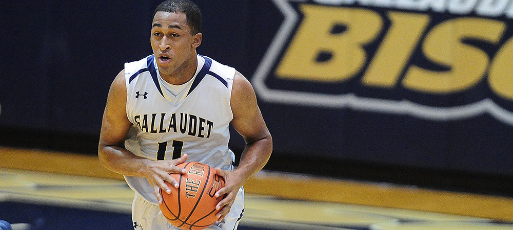 Gallaudet men's basketball player Jawaun Jackson brings the basketball up the court in the Gallaudet Field House. He wears a gray Gallaudet uniform with the #11 in navy lettering on his jersey.