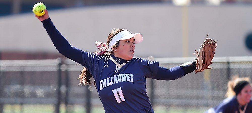 GU softball pitcher Jacklyn Zacarias winds up to make a pitch. Her right arm is back holding a neon yellow softball in her hand as she stares at home plate and the batter.