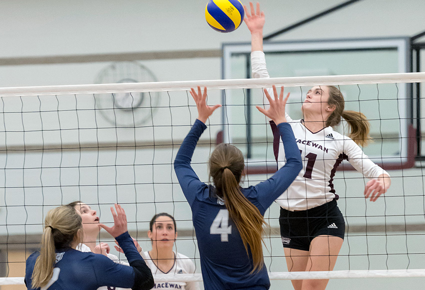 MacEwan's McKenna Stevenson hits over the Mount Royal University block during action last season. The two teams will meet this weekend among several preseason matches at the David Atkinson Gym (Chris Piggott photo).