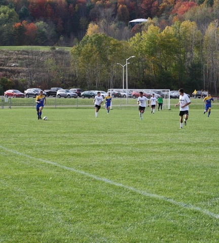SUNY Broome men's soccer players chasing opponent down the sideline