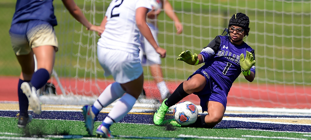 Gallaudet goalie Silvya Levesque makes a save in front of the goal in a purple GU soccer uniform.