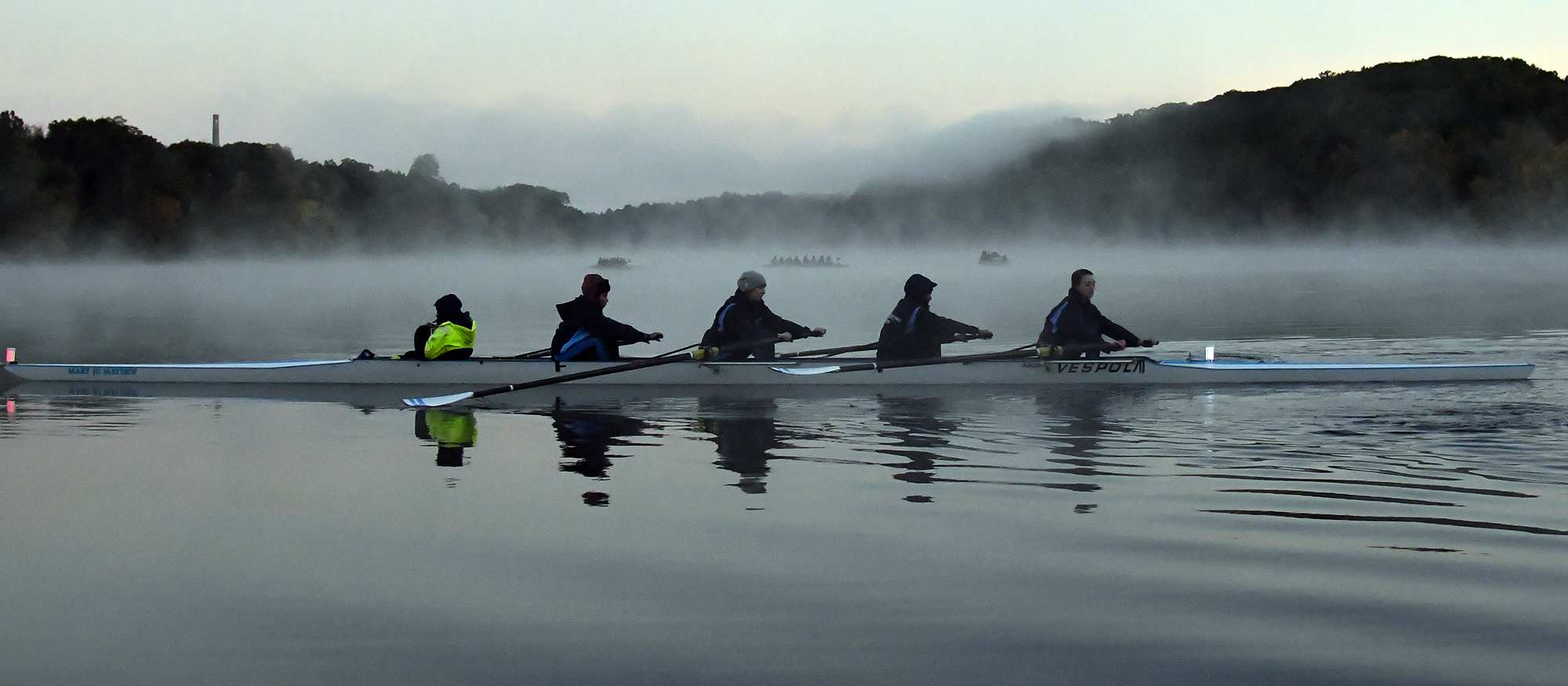 Action photo of a four-boat crew in rowing on the Connecticut River.