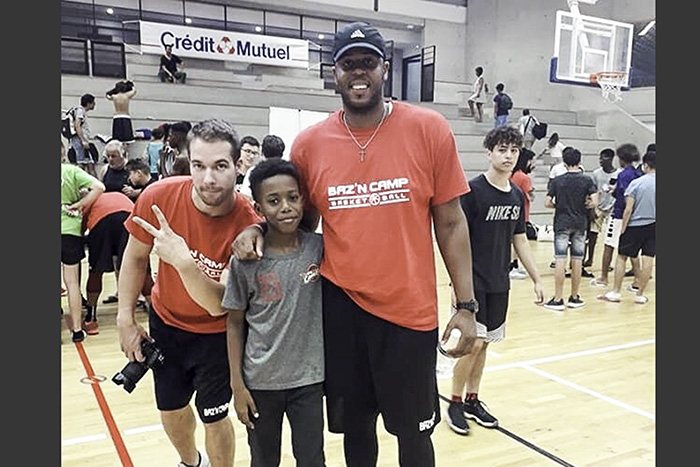 Head Coach Brandon Giles poses with campers at the Baz'n Camp in Marseilles, France.