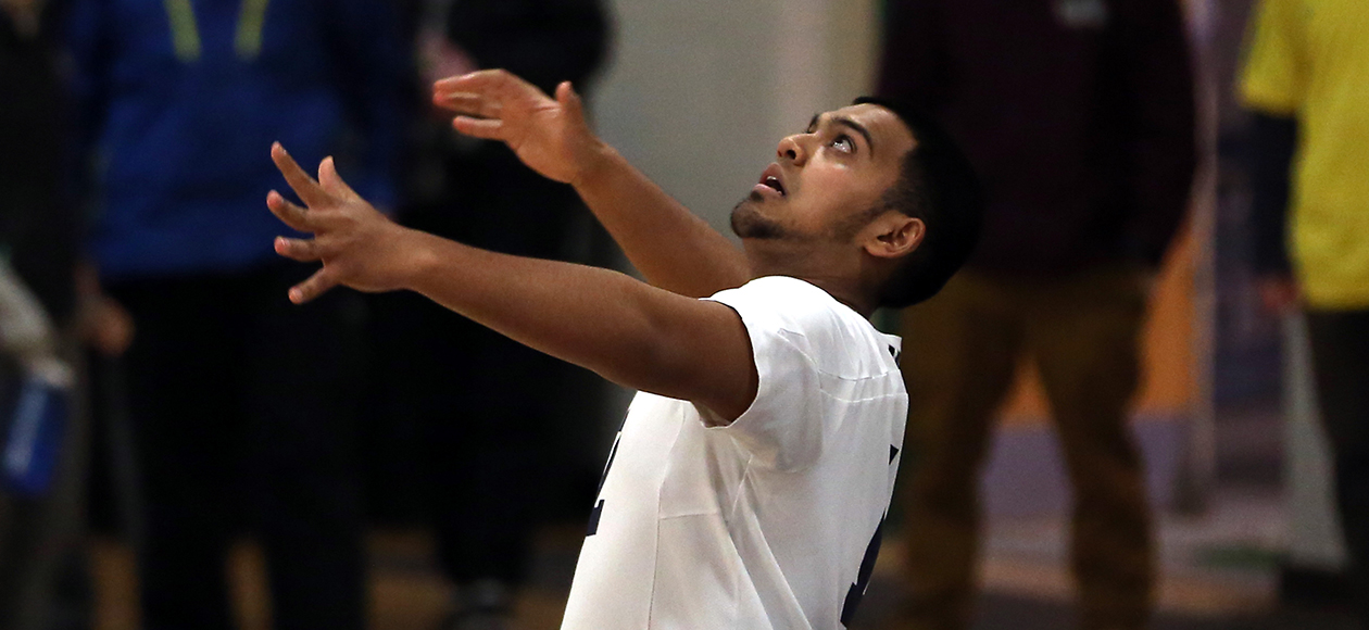 Amar Patel attempts to serve a volleyball.