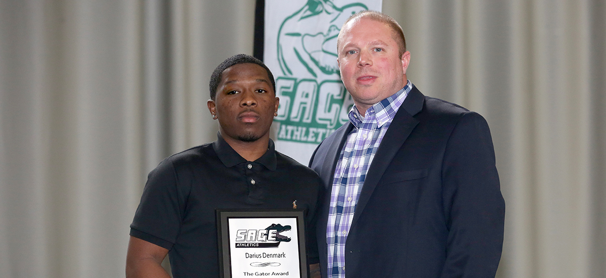 Darius Denmark honored as Gator of the Year in men's basketball as he is given the award from head coach Brian Barnes