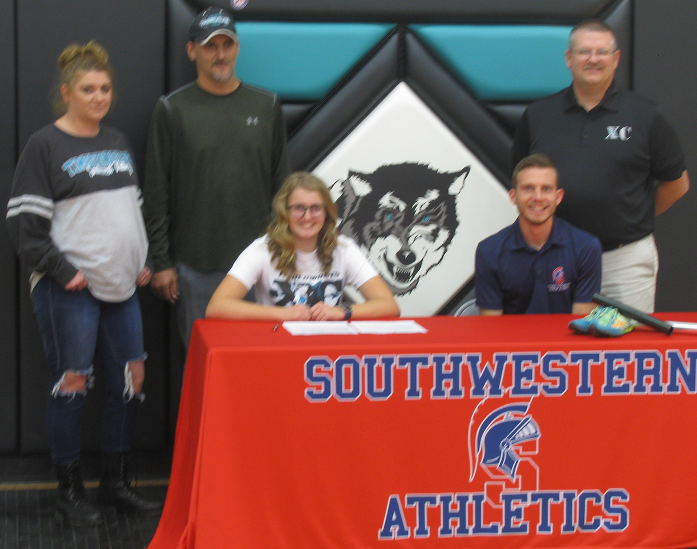 Maslyn Hummel, her family, and Southwestern Spartan Head Cross Country Coach Trey Bruton.