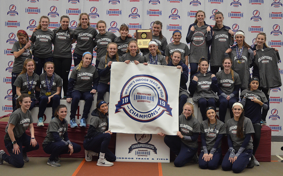 The women's track & field team on the podium after winning the 2019 Landmark Conference Indoor Championship at Susquehanna University.
