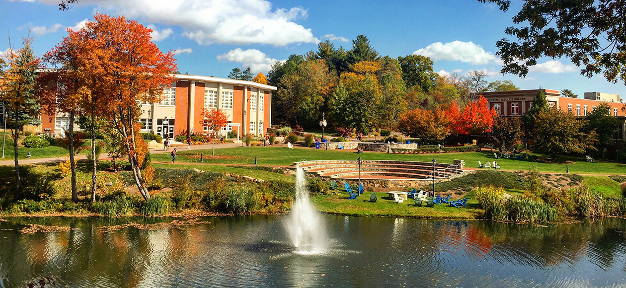 This is an image of the Endicott campus looking out at the Halle Library from across the pond and amphitheater on a gorgeous fall day with blue skies and bright orange leaves on the trees. The waterfall is flowing in the middle of the main pond.