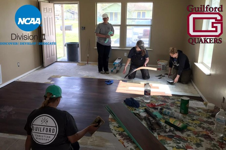 Guilford volleyball student-athlete Morgan Tompkins helps a team of volunteers lay flooring in a Texas home flooded by Hurricane Harvey.
