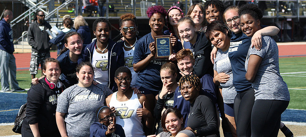 Gallaudet's women's track and field team picture after winning the home meet. Team holds first-place plaque.
