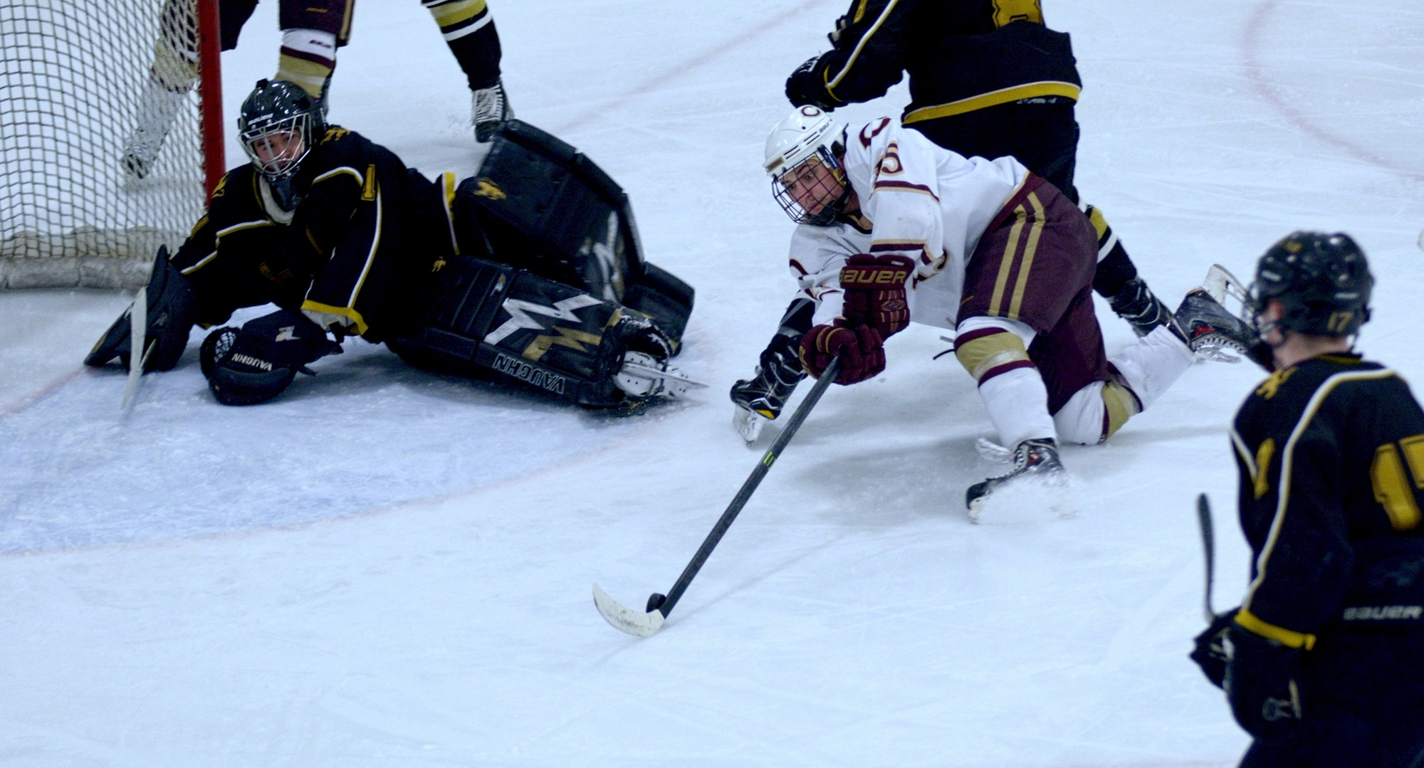 Junior Mario Bianchi reaches for a loose puck right in front of the St. Olaf during the Cobbers' series finale with the Oles.