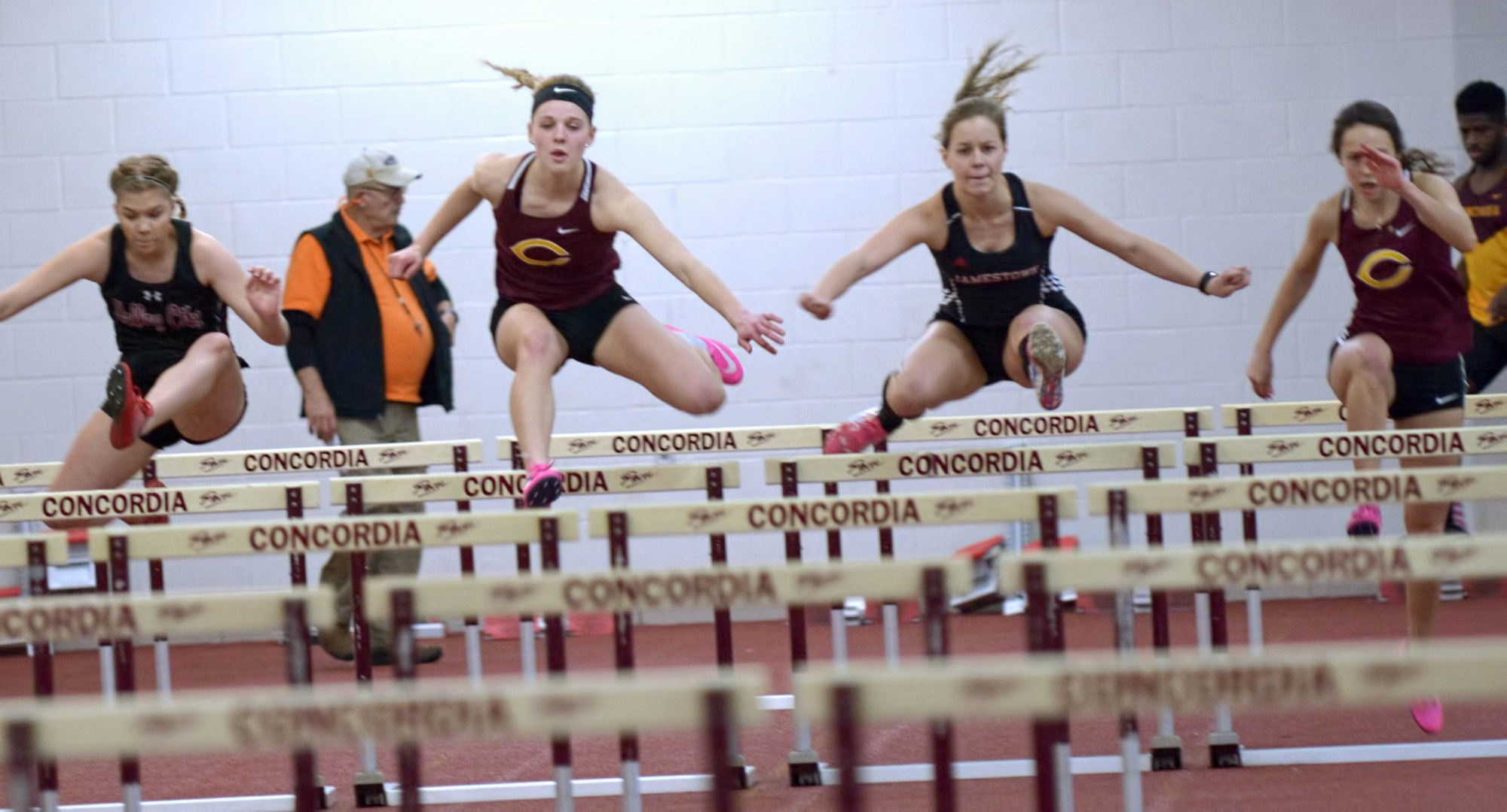 Runners jump out of the gate during the prelims of the 60-meter hurdles at the season-opening Cobber Open.
