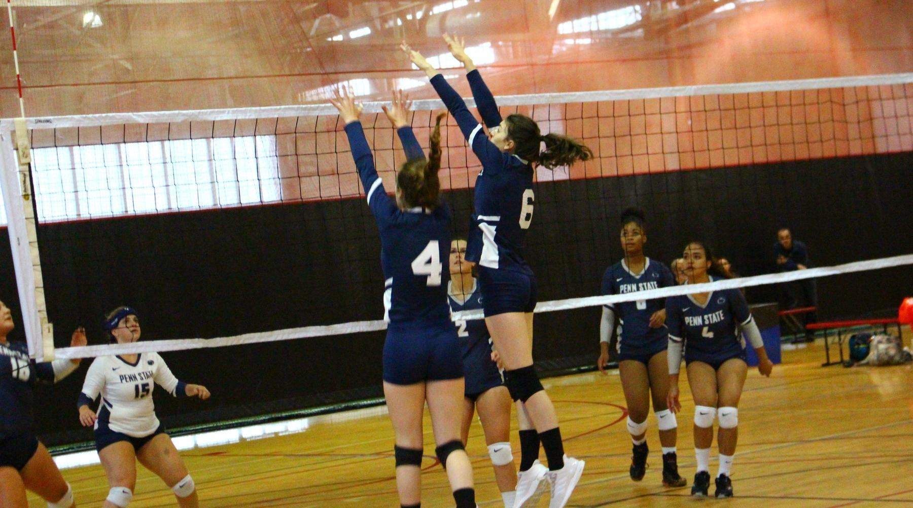 Two TKC volleyball players jump at the net attempting a block.