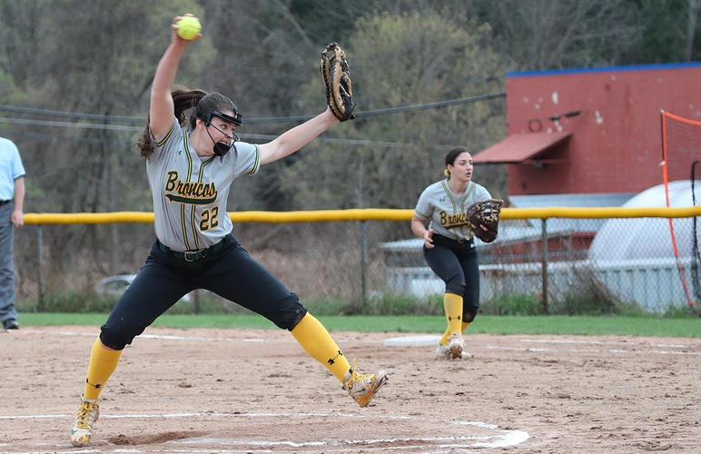 Haylee Lefebvre delivering a pitch, with first baseman Mackenzie Sparacino looking on.