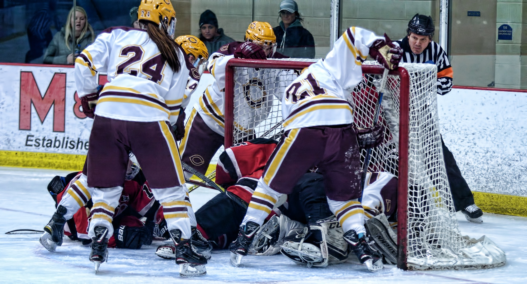 Players pile up in front of the Cobber goal, and netminder Amy Jost, during the third period of Concordia's contest with #6 Wis.-River Falls.