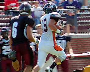 Kaleb Donahue sprints past an Earlham player on the way to the end zone.