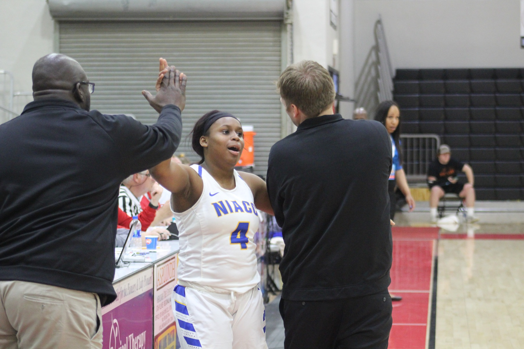 TT Longs gets high fives from NIACC coaches Todd Ciochetto and Jareese Willams Sr.