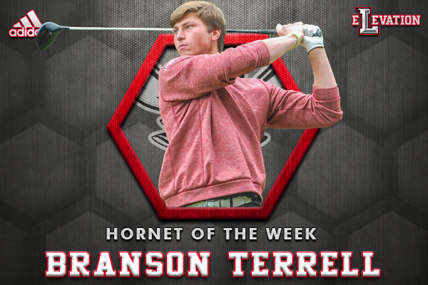 Branson Terrell watching a golf ball he's hit on top of the Hornet of the Week honeycomb-style graphic.