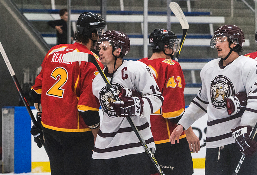 New captain Cam Gotaas shakes hands with University of Calgary Dinos players following a preseason game between the teams earlier this month at the Downtown Community Arena (Matthew Jacula photo).