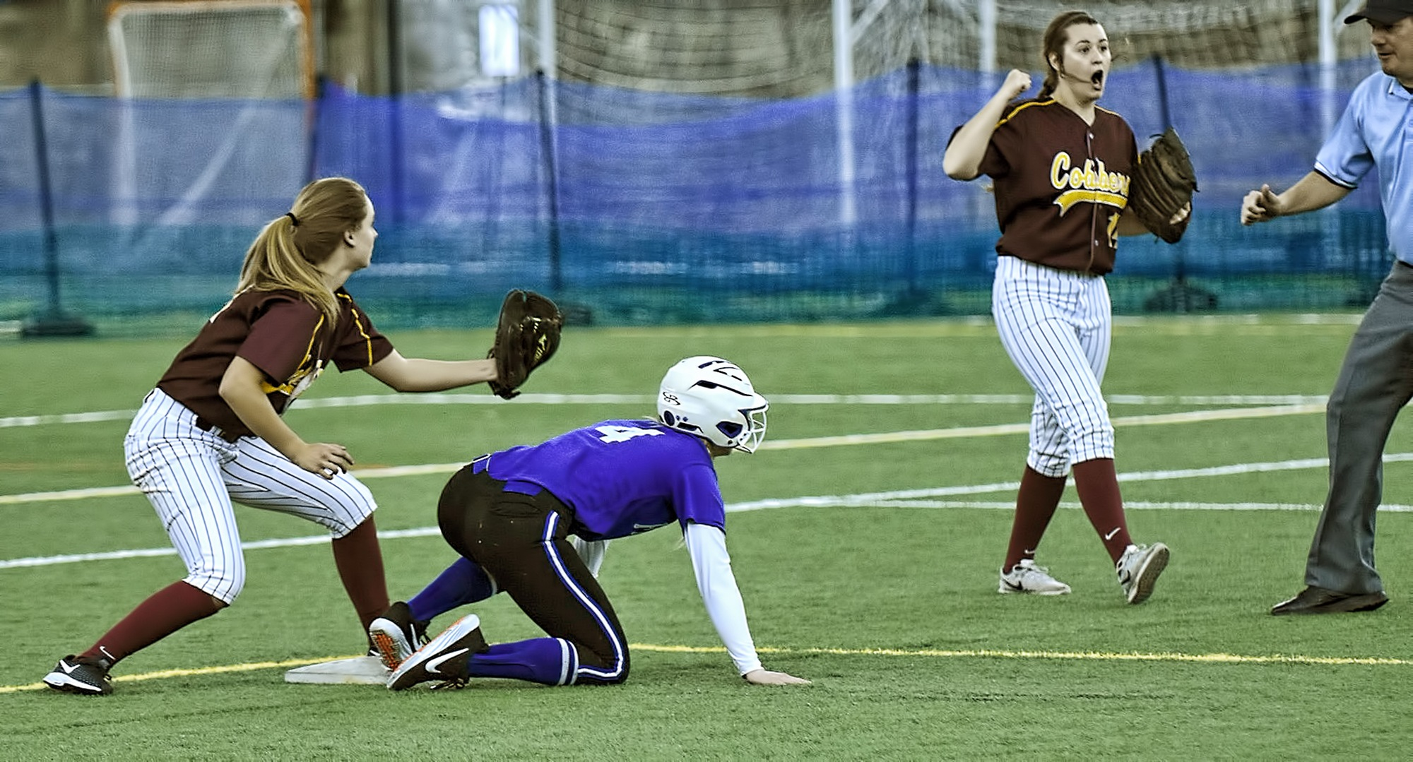 Shortstop Maria Pake show the umpire the ball after making a tag on a would-be stolen base attempt in the Cobbers' first game with Finlandia. Second baseman Kate Wensloff is helping the umpire make the call.