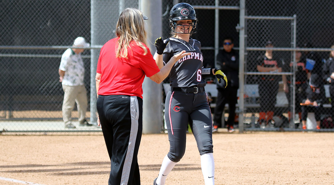 Michaela Foisy high-fives her coach at first base.