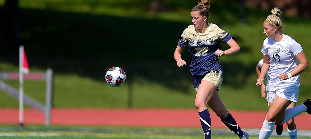 Gallaudet women soccer player Hannah Neild dribbles the ball away from a Keuka soccer player, in all white, right behind her. Neild has on GU's gold and blue uniform with the number 20 on the front, and GALLAUDET in gold lettering.