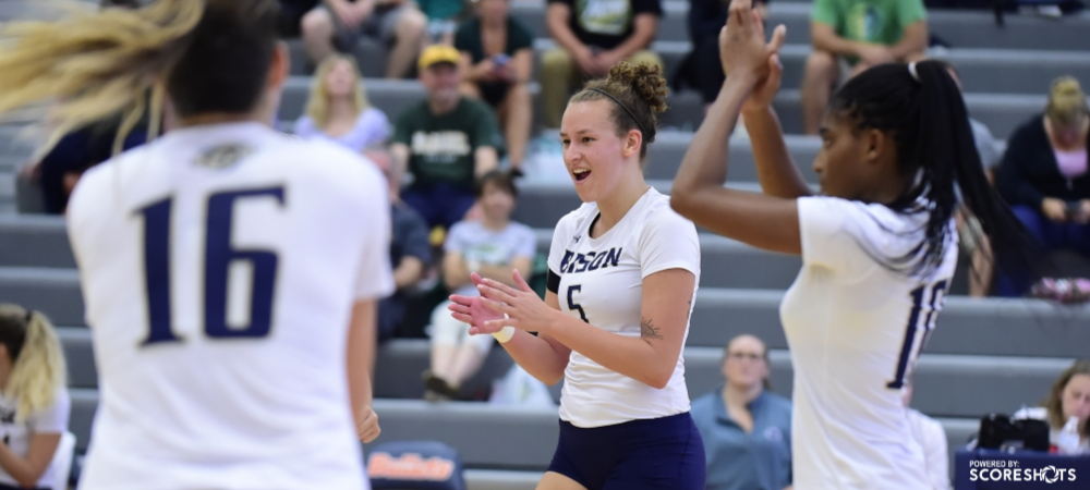 GU's Adele Daniels (center) and Shua Clay (right) celebrate a point during a volleyball match.