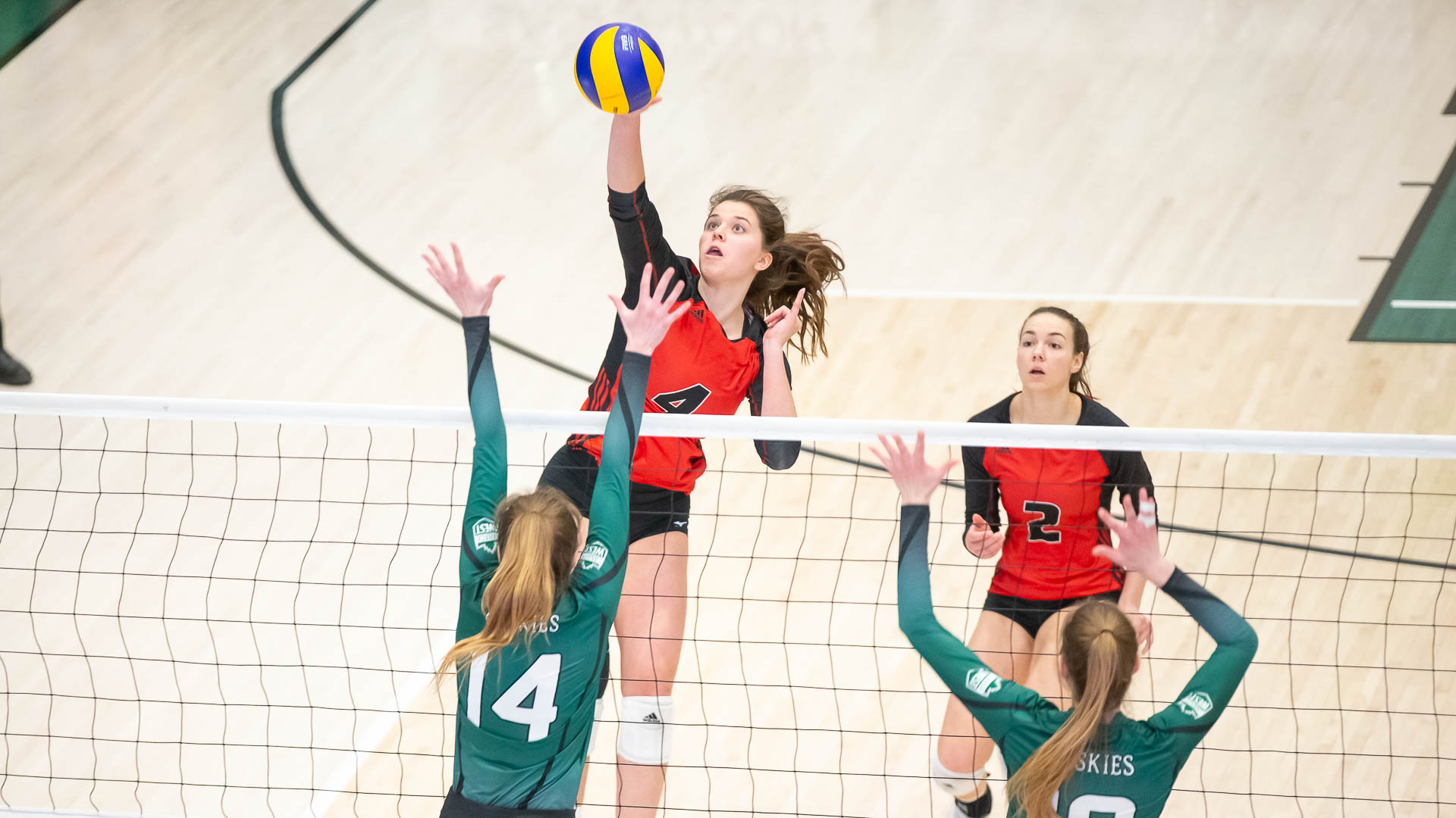 Middle blocker Taylor Boughton swings against the Saskatchewan Huskies block during women's volleyball action in Saskatoon, Saturday, Jan. 18, 2020. (Photo: Getmyphoto.ca)